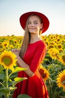 日の出のひまわりとフィールドで赤いドレスと帽子の美しい女性