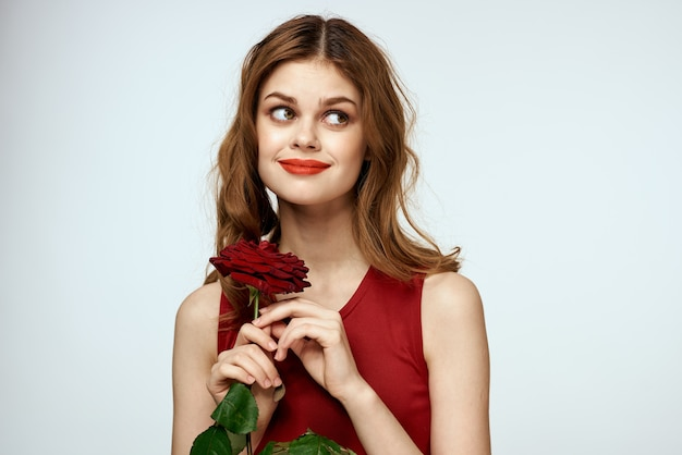赤いドレスを着た美しい女性はバラを保持します