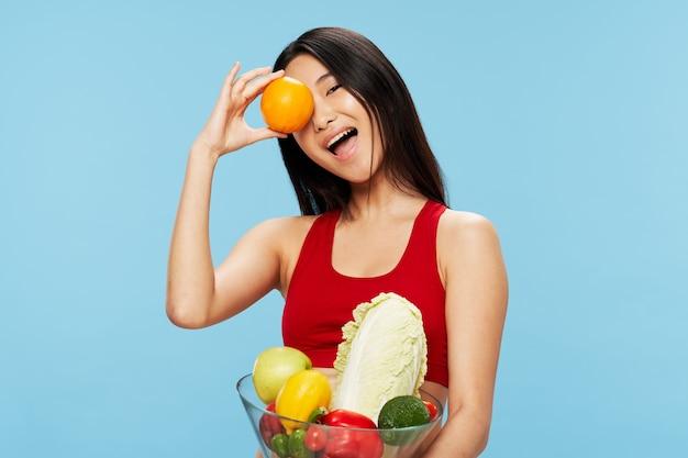 新鮮な野菜や果物の赤いタンクトップで美しい女性