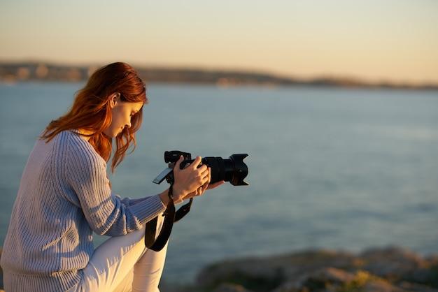 彼女の手にカメラを持つ海の近くのシャツとズボンの美しい女性