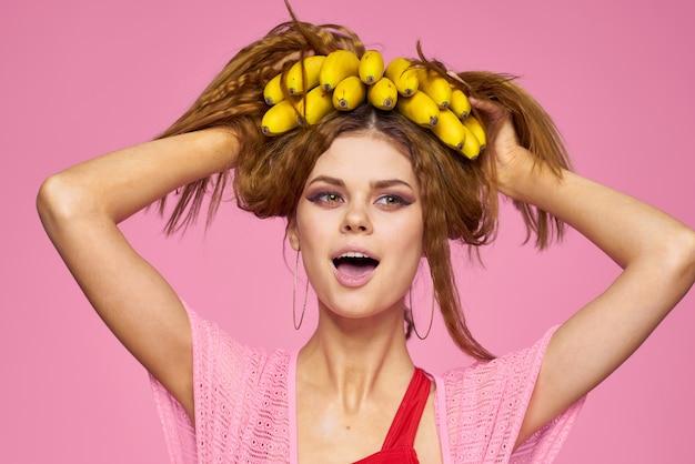 Красивая женщина в соломенной шляпе и в купальнике позирует на розовом фоне с бананами в руке, тропические пальмы