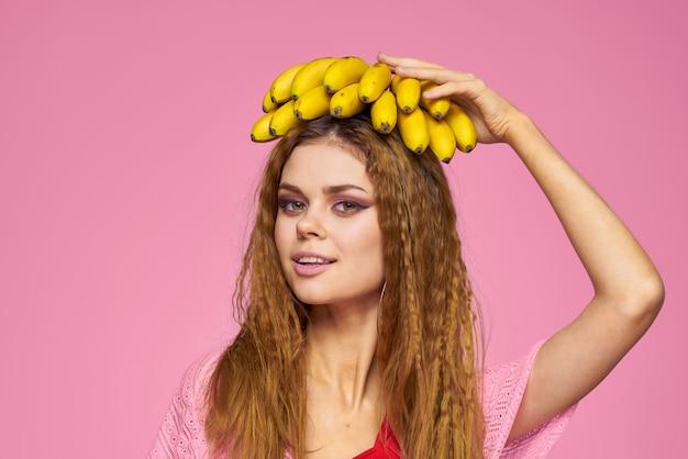 Красивая женщина в соломенной шляпе и в купальнике позирует с бананами в руке, тропические пальмы