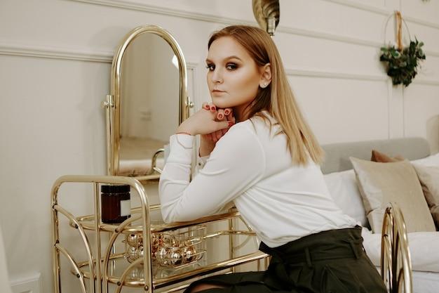 Красивая женщина в строгой белой блузке в своей комнате возле туалетного столика