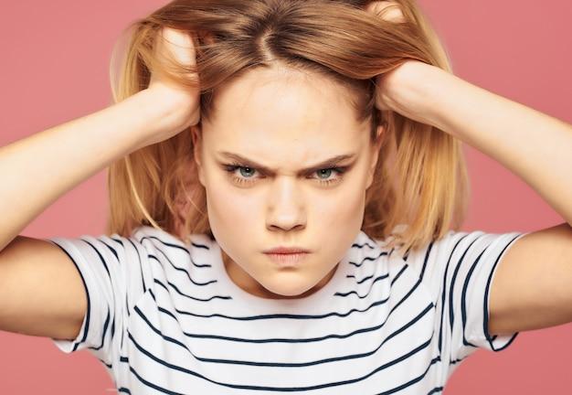 縞模様のtシャツの不満の美しい女性はスタジオピンクの背景を混乱させる