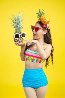파인애플을 들고 수영복에서 아름 다운 여자는 노란색에 포즈