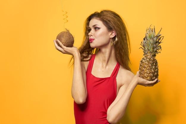 水着、赤い水着、トロピカルフルーツのココナッツとパイナップルと黄色の背景に面白い画像で美しい女性