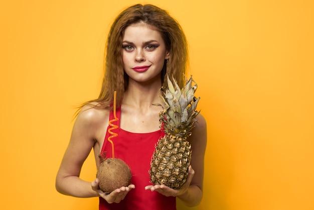 Красивая женщина в купальнике, красный купальник, забавное изображение на желтом пространстве с тропическими фруктами, кокосом и ананасом