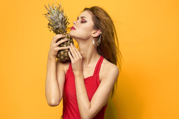 Красивая женщина в купальнике, красный купальник, забавное изображение на желтой стене с тропическими фруктами, кокосом и ананасом