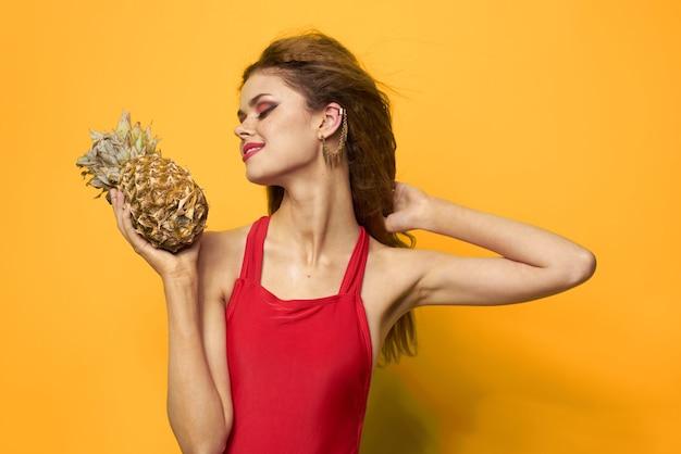 Красивая женщина в купальнике, красный купальник, забавное изображение на желтом с тропическими фруктами кокос и ананас