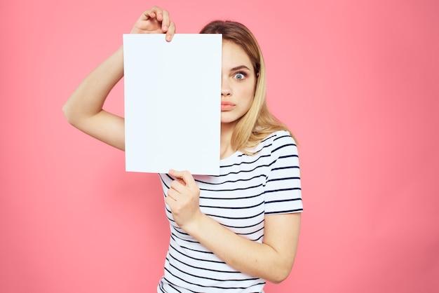 Красивая женщина в футболке держит чистый лист бумаги