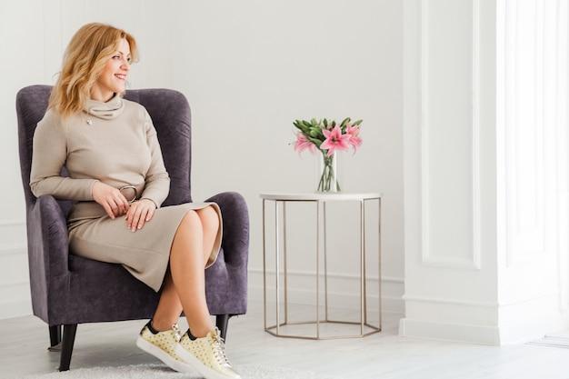 タイトなドレスとスニーカーの美しい女性が椅子に座って窓の外を見ています。