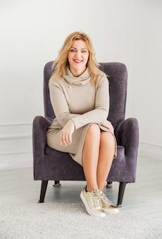 Красивая женщина в обтягивающем платье и кроссовках сидит в кресле, смотрит в камеру и улыбается. s