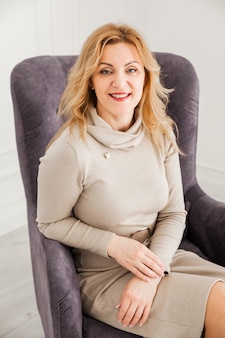 Красивая женщина в обтягивающем платье сидит в кресле, смотрит в камеру и улыбается. s