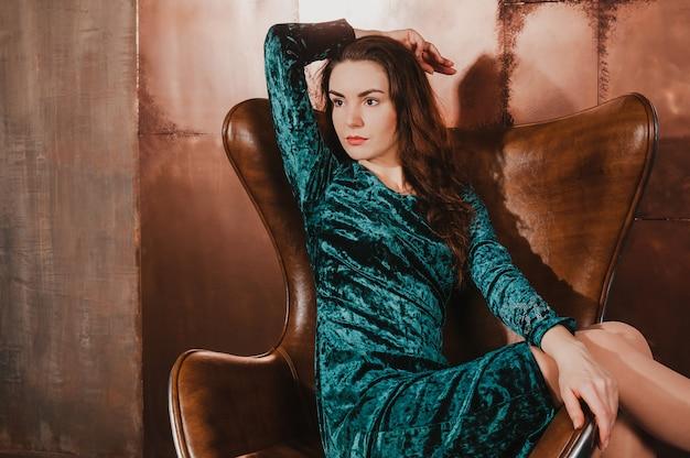 革の茶色の椅子に座って、ベルベットのドレスで美しい女性