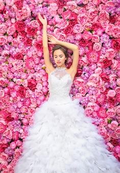 꽃 벽에 웨딩 드레스에서 아름 다운 여자