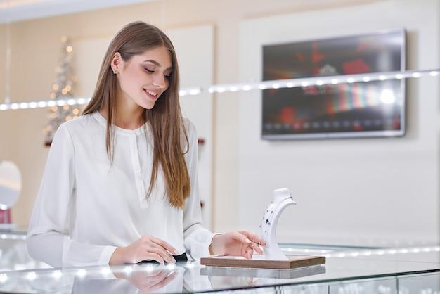 흰 블라우스에 아름 다운 여자는 보석 가게에서 목걸이를 찾고 있습니다