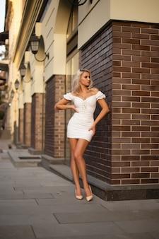 Красивая женщина в белом платье в городе он.