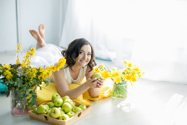 白いドレスを着た美しい女性は幸せと黄色い花の隣に屋内で笑顔