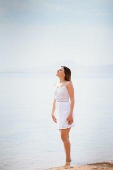 Красивая женщина в белом платье, идущем на пляже. Premium Фотографии
