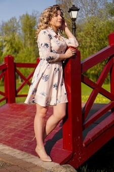 하얀 여름 드레스와 밀짚 모자에서 아름 다운 여자는 공원에서 자작 나무 다리에 서