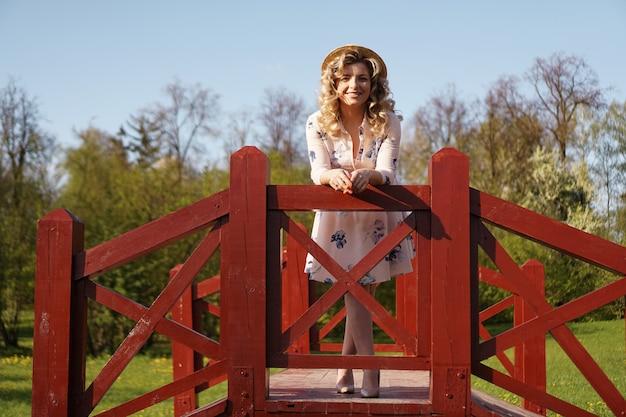白い夏のドレスと麦わら帽子の美しい女性が公園の白樺の橋の上に立っています