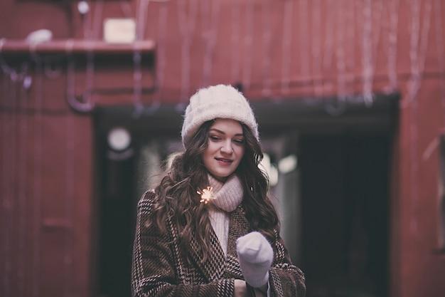 Красивая женщина в зимнем пальто и шляпе с бенгальским огнем