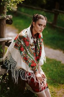Красивая женщина в вышитом традиционном платье сидит на скамейке и смотрит