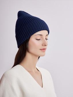 Красивая женщина в осенней шляпе на белом фоне. осенняя теплая одежда