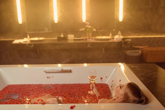 バラの花びらがワインを飲むとお風呂で美しい女性