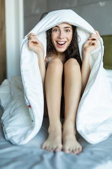 Красивая женщина в постели под пуховым одеялом с улыбкой