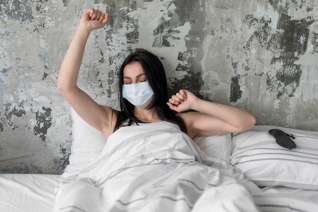 フェイスマスクが付いているベッドで美しい女性