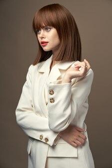 手で身振りで示すベージュのジャケットで美しい女性