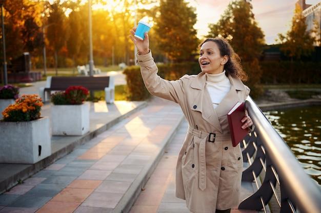 베이지색 트렌치 코트를 입은 아름다운 여성이 아름다운 가을날 도시 공원에서 핸드북과 테이크아웃 종이컵을 들고 걷는 동안 미소를 짓고 인사를 건넸습니다. 주말 야외