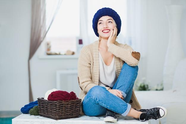 큰 파란색 니트 모자에 아름 다운 여자 실내 바구니 원사와 가슴에 앉아
