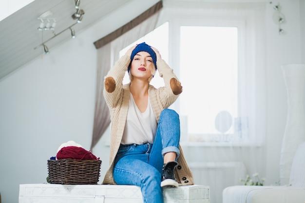 큰 흰색 니트 모자에 아름 다운 여자 실내 바구니 원사와 가슴에 앉아