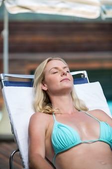 Красивая женщина в бикини, расслабляясь на шезлонге
