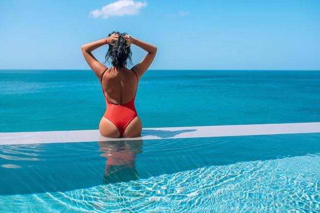 Красивая женщина в бикини, сидя на краю пейзажного бассейна