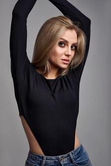 Красивая женщина в черном боди и джинсах