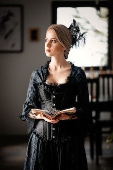 Красивая женщина в черном платье держит книгу и комнатные цветы лаванды