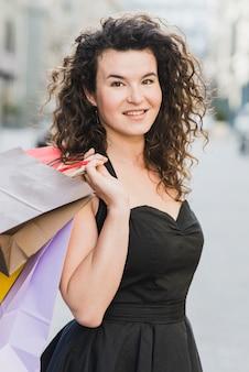 Beautiful woman in black dress holding shopping bags