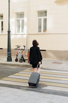 スーツケースと都市の風景の背景に黒のドレスの美しい女性