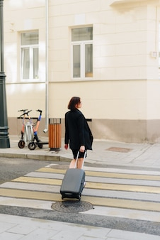 Красивая женщина в черном платье на фоне городского пейзажа с чемоданом