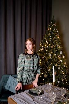 部屋の豊かなインテリアの豪華なクリスマスツリーの背景に黒のエレガントなドレスの美しい女性