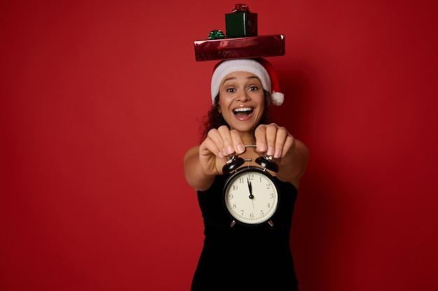 검은 이브닝 드레스와 산타 모자를 쓴 아름다운 여성은 머리에 선물 상자를 얹고 이빨 미소를 짓고 카메라를 보며 밤 12시경 알람 시계를 보여줍니다. 크리스마스 컨셉