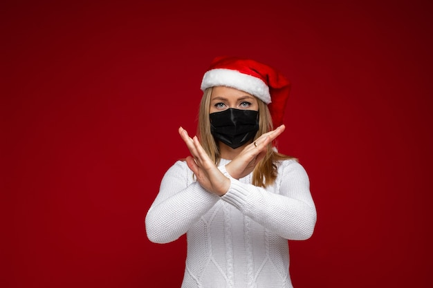 검은 얼굴 마스크와 빨간 산타 모자와 금지 제스처를 보여주는 흰색 스웨터에 아름 다운 여자. 붉은 벽에 격리. 코로나 바이러스 보호.