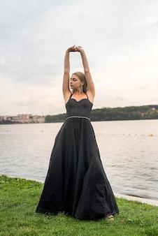 湖、夏の時間の近くでポーズをとって黒いファッションドレスの美しい女性