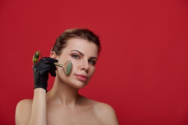翡翠のローラーで彼女の顔をマッサージする黒い手袋の美しい女性