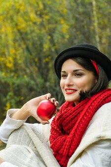 그녀의 손에 빨간 사과와 검은 모자와 빨간 스카프에 아름 다운 여자. 가을 야외 피크닉