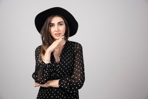 그녀의 턱을 잡고 검은 모자에 아름 다운 여자입니다.