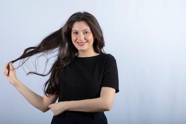 Красивая женщина в черном наряде позирует на белой стене.